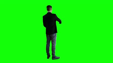 adam : A man in a jacket standing with his back against the background of a green screen