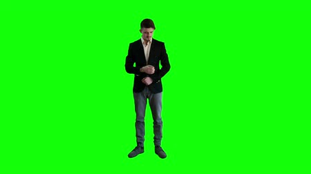 klucz : A man in a jacket standing at background of a green screen