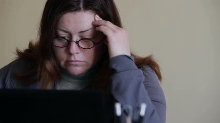 duro : Woman in office working at a laptop - tired