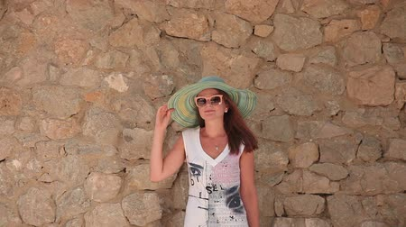 шляпа : Woman in hat near a stone wall