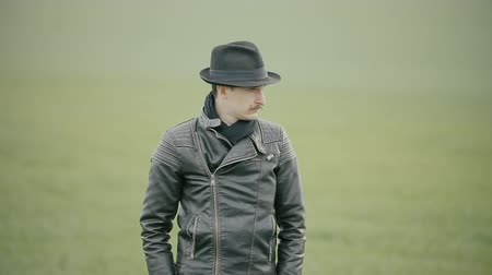bigodes : A man in a leather jacket and hat