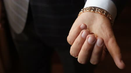 кулак : the hand squeezes wedding rings in a fist