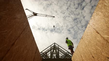осмотр : construction worker holding a set of plans, looking up at roof beams