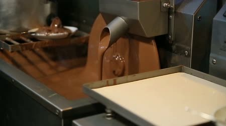 biała czekolada : Chocolate machine rotating disk with chocolate at candy factory. Wideo
