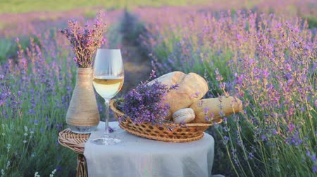 winnica : Glass of wine on the canvas cloth. White vase with flowers against lavender landscape in sunset rays. Sunset over a violet lavender field in Provence, France.