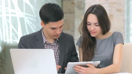 employee : Young attractive business man and woman discussing collating data on the tablet
