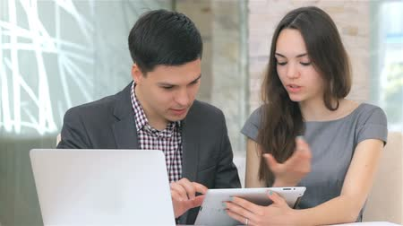 főnök : Young attractive business man and woman discussing collating data on the tablet, camera slide