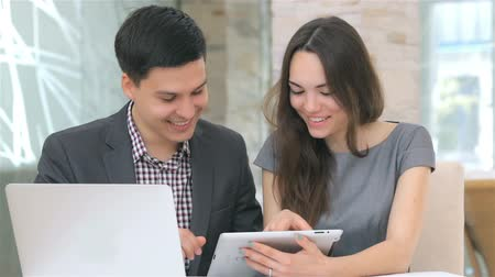 employee : Young attractive business man and woman discussing collating data on the tablet, camera slide