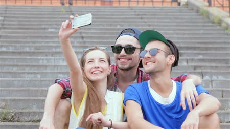 self portrait photography : Cheerful girl sitting on the steps of his friends makes selfie Stock Footage
