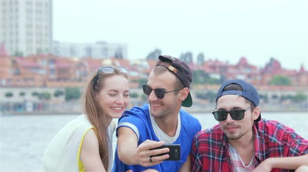 self portrait photography : Three friends sitting and laughing at the river and pictures of each other Stock Footage