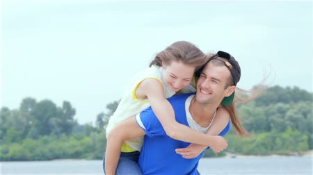 jumped : Girl guy jumped on his back and they run on the beach. Slow Motion. Stock Footage