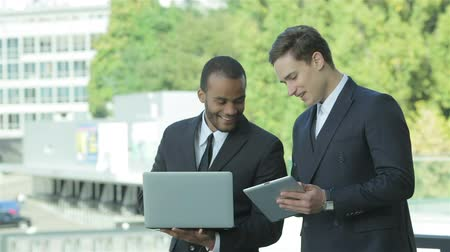corporate affairs : Business affairs. Two confident businessman holding a tablet and a laptop Stock Footage