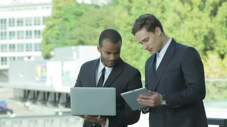 dialog : Business objectives. Two businessman holding a tablet and laptop in hand