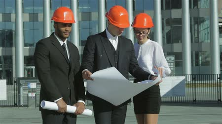 осмотр : Three confident business architect in protective helmet standing on the site Стоковые видеозаписи