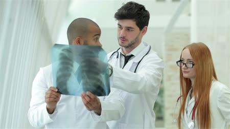 gravata : Three confident doctor examining x-ray snapshot of lungs in hospital
