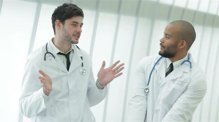 gravata : Two young doctors in medical gown lively debating