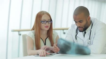gravata : Doctor talking to patient and keeps chest X-ray in hands Stock Footage