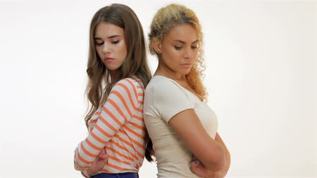 két : Two young girlfriends standing together. Brown-haired caucasian and red-haired mulatto girls quarreled and stand backs to each other. Two girls on a white background Stock mozgókép