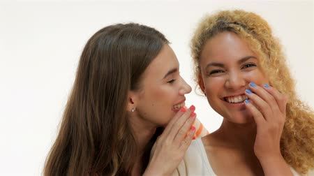 kulaklar : One woman said softly in his ear the other, isolated on white background. Two young girlfriends standing together. Brown-haired caucasian and red-haired mulatto girls on a white background Stok Video