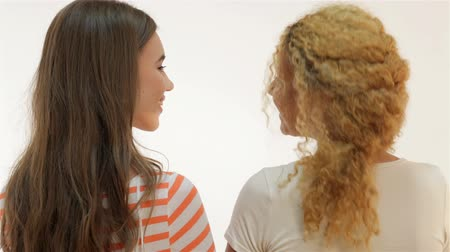 legjobb : Two nice young woman embracing and smiling while standing half-turned. Brown-haired caucasian and red-haired mulatto smiling at the camera and then look at each other. Two girls on a white background