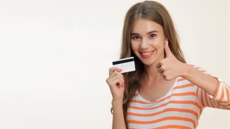 kart : Happy woman showing thumbs-up with credit card. Closeup portrait of young smiling woman holding credit card and showing thumb up sign, isolated on white background. Stok Video