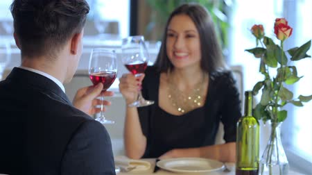ebéd : Call the waiter. Romantic dinner in the restaurant. Young couple sitting at a table at each other and smiling lovingly at the restaurant while toasting with wine. Young loving couple visits a restaurant. Romantic encounter. Celebrating a wedding anniversa
