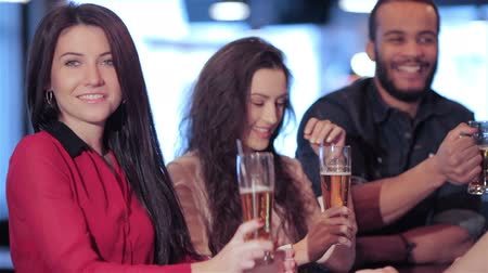 друзья : Cheerful company of guys and girl celebrating at the bar. The company has a rest after work. Cheerful company relax and have fun in the pub. Boys and girls cheering for their football team and drink beer