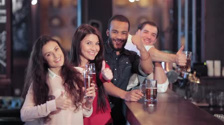baví : Cheerful company of guys and girl celebrating at the bar. The company has a rest after work. Cheerful company relax and have fun in the pub. Boys and girls cheering for their football team and drink beer