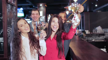 cümbüş : Cheerful company of guys and girl celebrating at the bar. The company has a rest after work. Cheerful company relax and have fun in the pub. Boys and girls cheering for their football team and drink beer