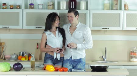mutfak malzemesi : Couple in love drinking grape juice and kissing in the kitchen. Young smiling friends cook dinner in kitchen while cut vegetables. Food cooking together.