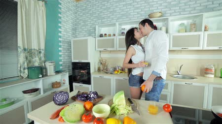 mutfak malzemesi : Panorama kitchen which meets the new couple with orange fresh. Young smiling friends cook dinner in kitchen while cut vegetables. Food cooking together. Stok Video