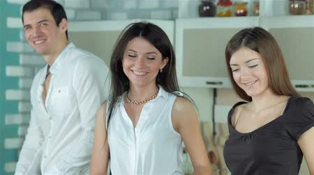panelas : Three friends are preparing themselves healthy dinner and smiling directly at the camera. Young smiling friends cook dinner in kitchen while cut vegetables. Food cooking together.