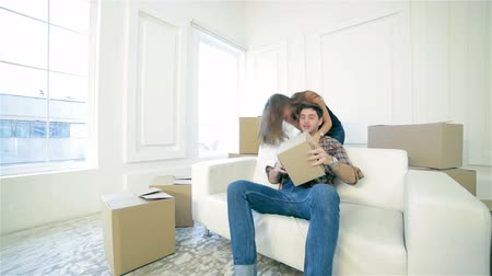 subir : Shifting a family. Love couple sitting on the couch and show a thumbs up while young and beautiful couple in love sitting in an empty apartment among boxes Vídeos