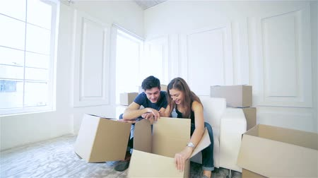 home life : Shifting to new life. Couple in love moving and keep a box in his hands and looking inside box while a young and beautiful couple in love sitting on the couch in an empty apartment among boxes