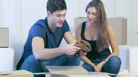 daireler : Dream come true, moving. Loving couple enjoys a new apartment and get things from the box in his hands while young and beautiful couple in love sitting on the couch in an empty apartment among boxes