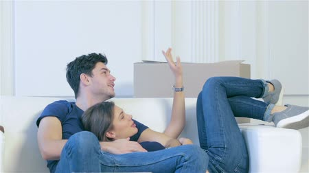 apartamentos : Moving home and repair of a new life. Couple in love lying on sofa among boxes for moving while man and woman hugging together in an empty apartment