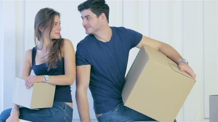 ипотека : Moving, repairs, new apartment. Couple girl and the guy kept moving boxes in hands and looking at the camera while man and woman are standing behind the couch among boxes in an empty apartment
