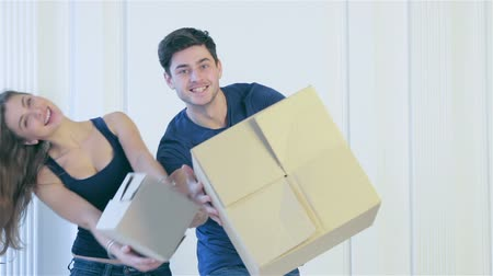 apartment : New repair and relocation. Loving couple enjoys a new apartment and keep the box in his hands while young and beautiful couple in love standing behind couch in an empty apartment among boxes Stock Footage