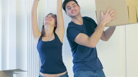 daireler : Moving, repairs, new apartment. Couple girl and the guy throw the box in hands while man and woman are standing behind the sofa among boxes in an empty apartment