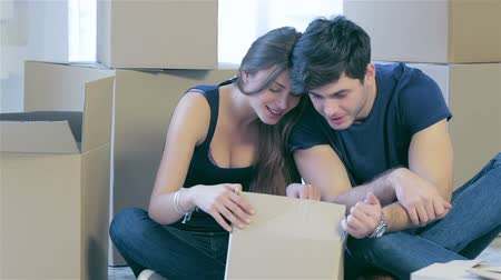 daireler : Shifting to new life. Couple in love moving and keep a box in his hands and looking inside box while a young and beautiful couple in love sitting on the couch in an empty apartment among boxes