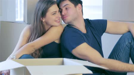 apartamentos : Moving, repairs, new house keys. Couple girl and the guy sitting on the floor among the boxes in an empty apartment and  kiss Stock Footage