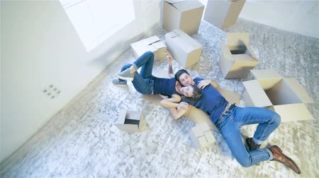 daireler : Moving, repairs, new home. Couple girl and guy lie on the floor in an embrace while man and woman lying on the floor among the boxes in an empty apartment