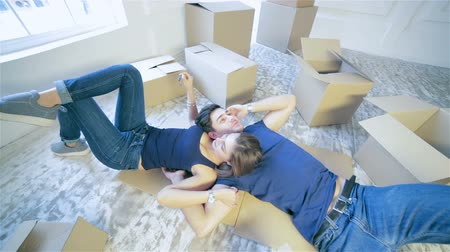 Moving,shifting, repairs, new keys to the apartment. Couple girl and the guy holding the keys to the apartment while man and woman lying on the floor among the boxes in an empty apartment