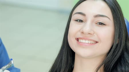 gülümseyen : The girl in the dental chair. Close-up face of a girl who looks at the dentist and then teeth smile right into the camera
