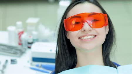 зубастая улыбка : Portrait of a girl at the dentist. Girl sitting in the dental chair in red protective glasses. Girl teeth smile directly at the camera