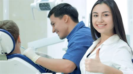 зубастая улыбка : New working day dentists. The dentist examines the teeth and smiles at him and the girl-assistant teeth smile directly at the camera and thumb up.
