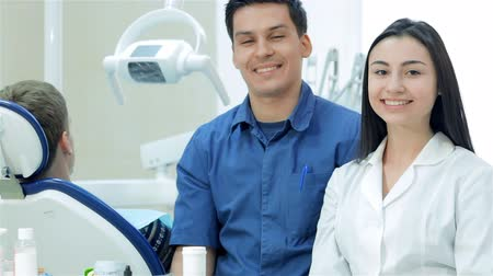 зубастая улыбка : New working day dentists. The girl-intern beside the the chef-dentist. They are teeth smile then thumbs up