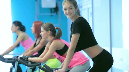 atlet : Workout in the gym. Athletic girl pedaling and looking at the camera on a stationary bike at the gym while her girlfriend athletes pedaled on bicycles in the background Stok Video