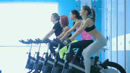 four legs : A great workout. Sport girl pedaling on the simulator while four friends athletes pedaling on a stationary bike at the gym show thumbs up Stock Footage