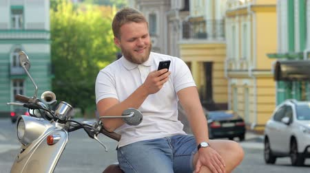 борода : Handsome bearded young man is sitting on scooter with smartphone. Man is sitting on scooter and looking at the smartphone. Стоковые видеозаписи